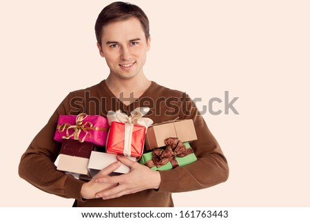 young cheerful man holding lots of gifts (retro) - stock photo