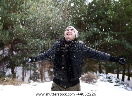 Young cheerful man under snowing. - stock photo