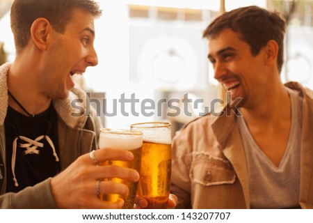 Young cheerful men having fun drinking beer outdoors. - stock photo
