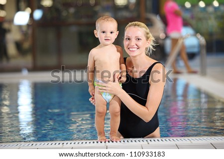 Young cheerful mother and little son looking at the camera at the edge of a swimming pool - stock photo