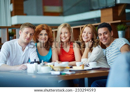 Young cheerful people sitting at caf���© - stock photo
