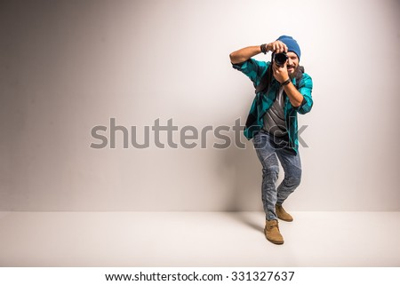 Young cheerful photographer with beard, while working in studio - stock photo