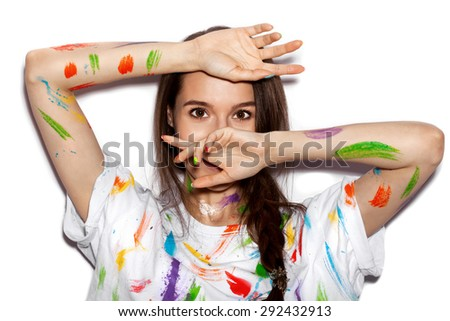 Young cheerful soiled in paint girl having fun. Woman with bright makeup and hairstyle covering her face with her hands on White background not isolated - stock photo