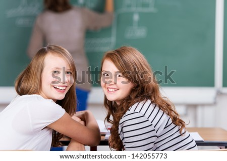 Young cheerful students during the class in schoolroom - stock photo