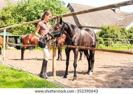 Young cheerful teenage girl-equestrian stroking big chestnut horse. Vibrant multicolored summertime outdoors horizontal image. - stock photo
