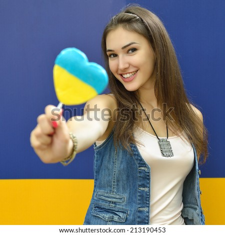 Young cheerful woman holding candy painted in colors of ukrainian flag. Ukrainian patriot concept.  - stock photo