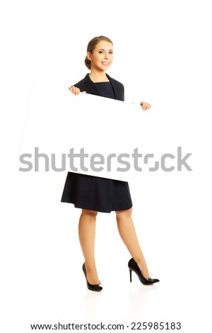 Young cheerful woman holding white banner - stock photo