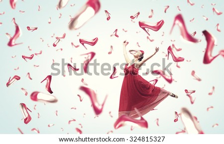 Young cheerful woman in dress and many falling shoes - stock photo