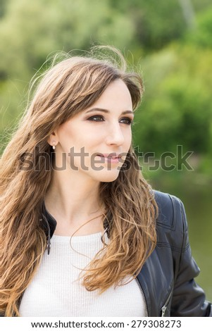 Young cheerful woman looking sideways at  outdoors. Beauty Caucasian girl outdoor portrait - stock photo
