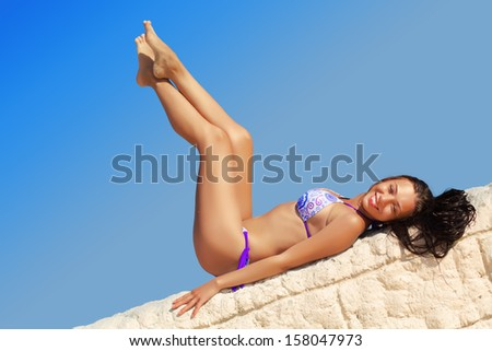 Young cheerful woman lying on the stone wall - stock photo