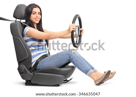 Young cheerful woman pretending to drive seated on a car seat isolated on white background - stock photo