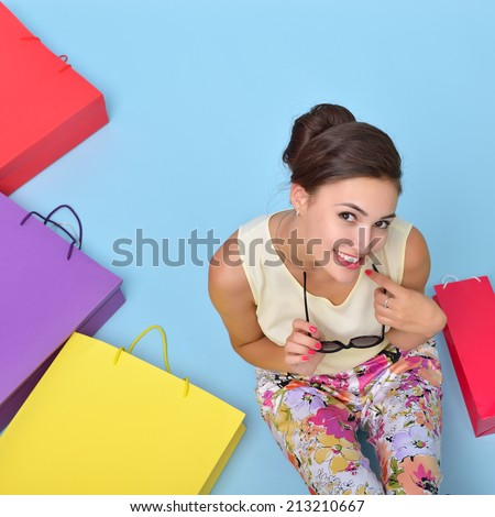 Young cheerful woman with colored paper shopping bags. Shopaholic. Shopping concept and ideas. Urban lifestyle. - stock photo