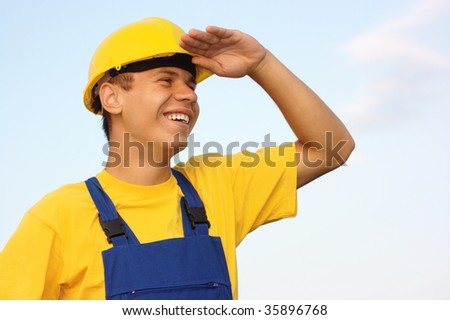 Young cheerful worker looking forward, covering eyes from the sun, dressed in blue-and-yellow uniform and hard hat, over blue sky - stock photo