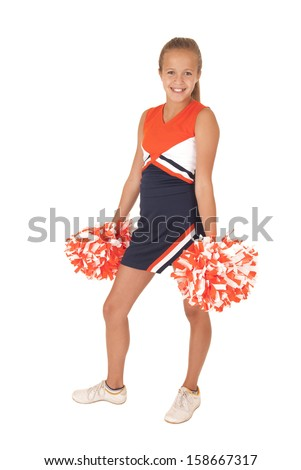 Young cheerleader standing with pompoms down low - stock photo