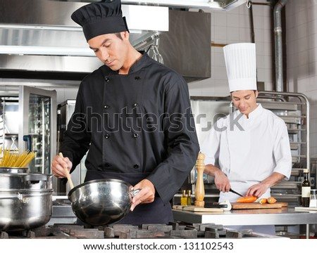 Young chef cooking food with male colleague chopping vegetable in background - stock photo