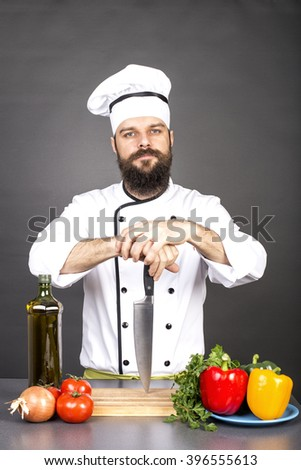 Young chef holding a big sharp knife on a board ready to cook over gray background - stock photo