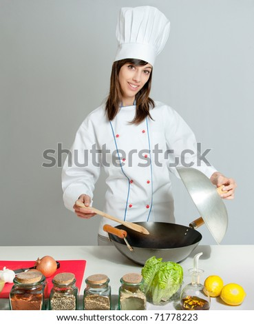 Young chef in a neutral background giving a cooking lesson - stock photo