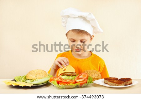 Young chef puts cheese on the hamburger - stock photo