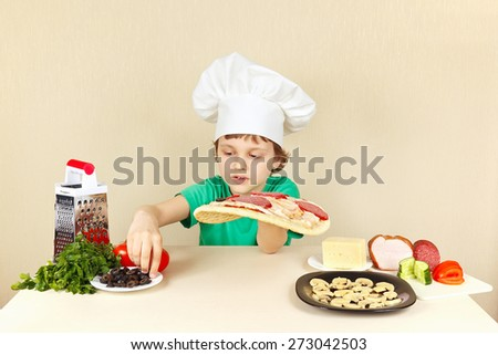 Young chef puts olives on the pizza crust - stock photo