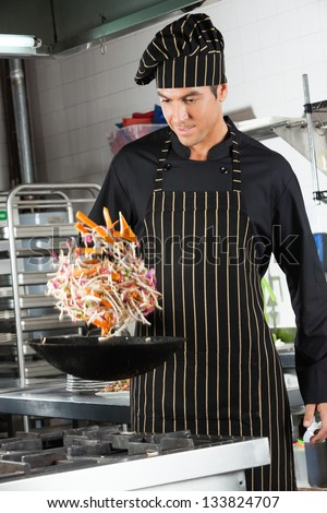 Young chef tossing vegetables in a wok in an industrial kitchen - stock photo