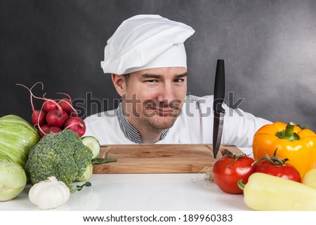 Young chef with knife and vegetable on black background - stock photo