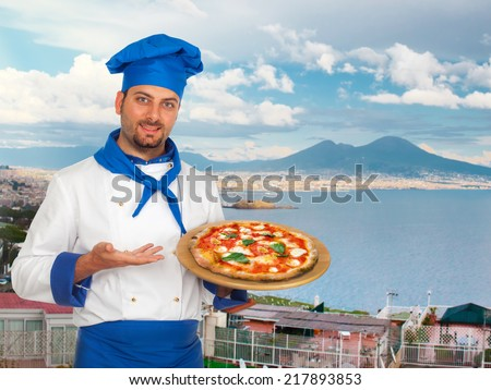 Young chef with neapolitan pizza margherita with Gulf of Naples in background. - stock photo