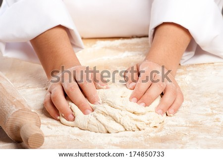 young chef working the dough with hands   - stock photo