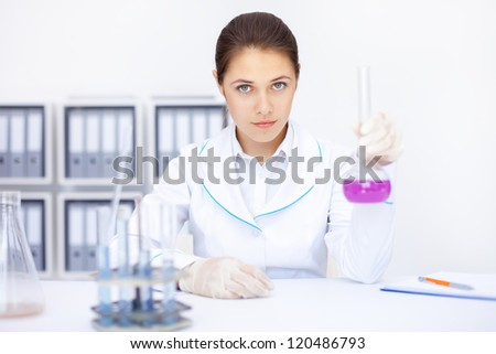 Young chemical female researcher working with chemicals in laboratory - stock photo