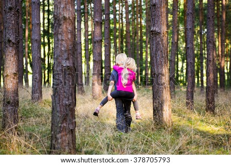 Young child boy giving his sister piggyback outdoors in the forest - stock photo