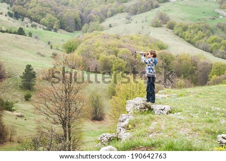 young child boy looking through binocular to the country side on natural background - stock photo