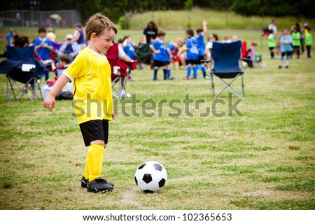 Young child boy playing soccer during organized league game - stock photo