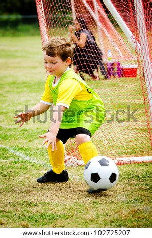 Young child boy playing soccer goalie during organized league game - stock photo
