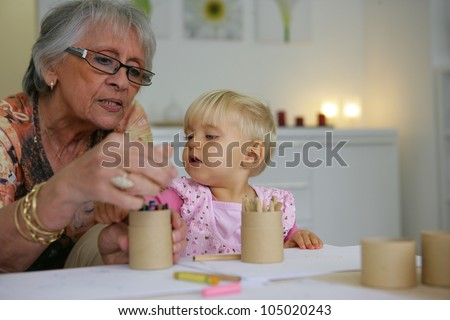 Young child coloring with grandma - stock photo