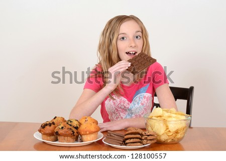 young child eating large chocolate bar - stock photo