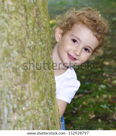 Young child, girl, outside, laughing as she hides behind a tree. - stock photo