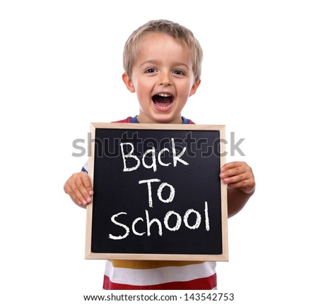 Young child holding back to school chalk blackboard sign standing against white background - stock photo
