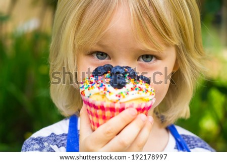 Young child holding colorful homemade cupcake with berries and sprinkles - stock photo