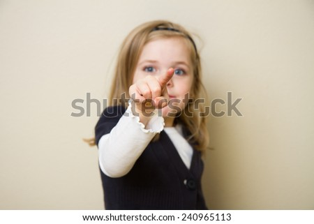 Young child holding her hand up pointing into the air. Focus is shallow and centered on the hand and finger of the child - stock photo