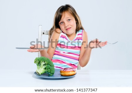 Young child in a food choice dilemma, shrugs her shoulders in confusion, broccoli or donut? - stock photo
