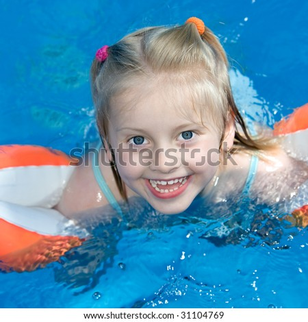Young child is swimming in a pool - stock photo