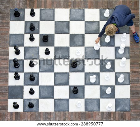 Young child making a move on an outdoor chessboard, seen from above - stock photo