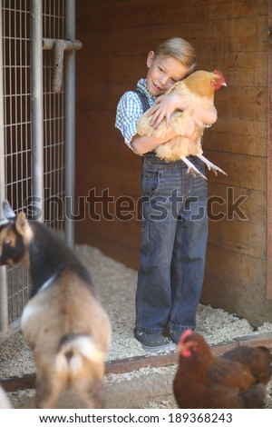 Young Child on a Farm With Animals - stock photo