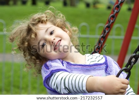 Young child playing on a swing at the playground. - stock photo