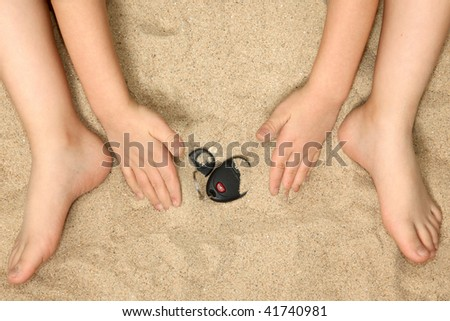 Young child's hands and feet in sand playing with car keys. - stock photo