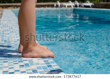 Young child standing barefoot at the edge of a swimming pool just above the inviting cool blue water, closeup view of the legs - stock photo
