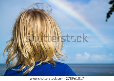 Young child watching a rainbow over the ocean - stock photo