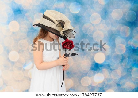 Young child wearing an over sized hat, holding a red rose with a blue background - stock photo