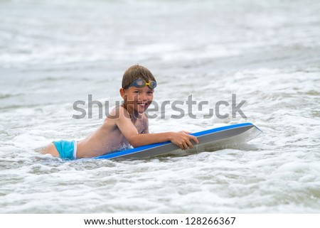 Young child with a bodyboard on the beach - stock photo