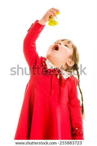 Young child with green grapes in hand and open mouth - stock photo