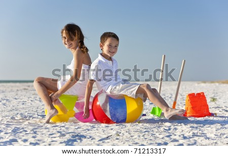 Young children, boy and girl, brother and sister, having fun, playing on a beach with beach balls, buckets and spades - stock photo